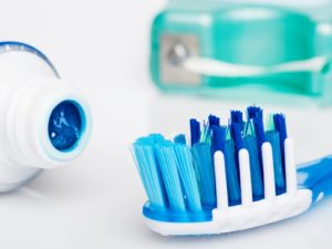close up of a toothbrush, toothpaste and dental floss