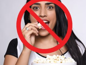 Image of teen eating popcorn. A big red cross is overlayed to indicate-do not eat popcorn when wearing braces